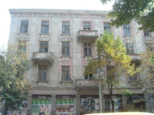 """А това е именно сградата в отражението – някогашният хотел Париж. Сградата е проектирана от известния български архитект Наум Торбов (автор също на проекта за Халите) и е завършена през 1908 г. През 1942 г. е сключен предварителен договор за продажбата му, който така и не става окончателен заради събитията от края на 1944 г. По времето на социализма хотелът е преименуван на """"Здравец"""". През 90-те е реституиран на два пъти – по веднъж на всяка от страните по предварителния договор за покупко-продажба. Вследствие на това, собствеността е неизяснена, а външният вид – красноречив."""